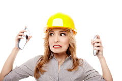 Stressed woman engineer using two cell phone at the same time Stock Image