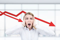 Stressed woman and falling graphs. Portrait of a stressed out businesswoman crying in dispair while standing in her office with two falling graphs in the Royalty Free Stock Photos