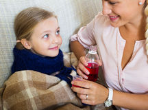 Stressed woman giving liquid medicine to little girl with grippe Stock Image