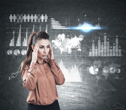 Stressed woman and graphs on blackboard Stock Image
