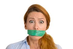 Stressed woman with green measuring tape covering mouth Royalty Free Stock Image