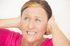 Stressed woman with hands on head. Portrait stressed and worried mature woman with hands on head, covering ears, isolated on white Royalty Free Stock Photos