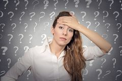 Stressed woman has many questions. Portrait stressed woman with headache has many questions  grey wall background with question marks. Human emotion face Stock Photos