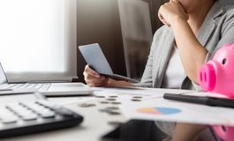 Stressed Woman holding account passbook. Calculator, Pink Piggy Bank, Laptop, business chart and graph document on desk. Debt Stock Images