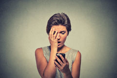 Stressed woman holding cellphone disgusted shocked with message she received Royalty Free Stock Photo