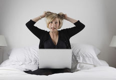 Stressed woman with laptop. Stressed young woman with laptop computer pulling hair on bed royalty free stock image