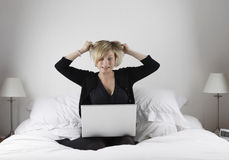 Stressed woman with laptop. Stressed young woman with laptop computer pulling hair on bed royalty free stock photos