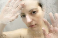 Stressed woman leaning on weeping glass shower door Royalty Free Stock Images