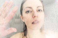 Stressed woman leaning on weeping glass shower door Stock Image