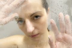 Stressed woman leaning on weeping glass shower door Stock Photo