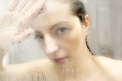 Stressed woman leaning on weeping glass shower door Royalty Free Stock Photos