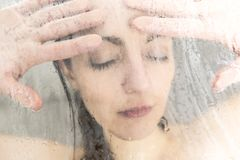 Stressed woman leaning on weeping glass shower door Royalty Free Stock Photo