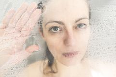 Stressed woman leaning on weeping glass shower door. A Stressed woman leaning on weeping glass shower door Stock Image