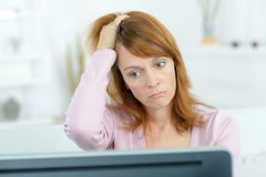 Stressed woman looking at computer screen Royalty Free Stock Photography