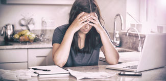 Stressed woman looking down at bills. In kitchen Royalty Free Stock Photography