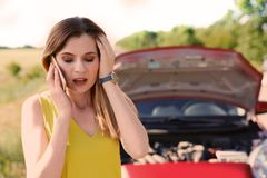 Stressed woman with mobile phone standing near broken car. In countrye royalty free stock image