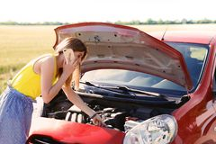 Stressed woman with mobile phone standing near broken car. In countrye royalty free stock photos