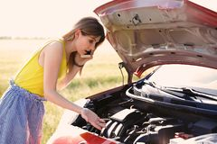 Stressed woman with mobile phone standing near broken car royalty free stock photo