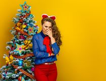 Stressed woman near Christmas tree isolated on yellow Royalty Free Stock Photography