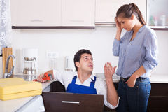 Stressed woman and nervous handymen near sink in kitchen Royalty Free Stock Images