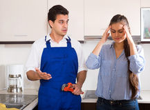 Stressed woman and nervous handymen near sink in kitchen Royalty Free Stock Photography