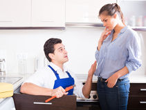 Stressed woman and nervous handymen near sink in kitchen Royalty Free Stock Photo