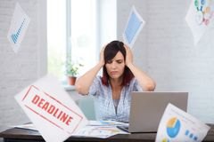 Stressed woman in office thinking about deadline. Stock Image