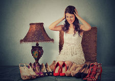 Stressed woman picking up the right pair of high heel shoes Royalty Free Stock Photography