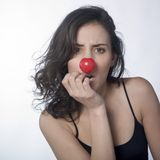 Stressed woman with red nose. A portrait of a stressed woman wearing red nose Royalty Free Stock Photos