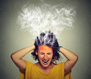 Stressed woman screaming frustrated thinking too hard steam coming out of head Royalty Free Stock Image
