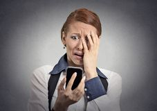 Stressed woman shocked with message on smartphone. Upset stressed woman holding cellphone disgusted shocked with message she received grey background. Funny royalty free stock photo