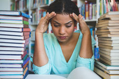 Stressed woman sitting amidst books in library Stock Image