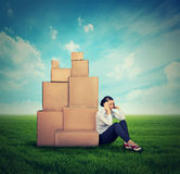 Stressed woman sitting on the ground green grass with many boxes Royalty Free Stock Photos