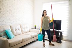 Stressed woman standing holding broom and bucket in living room. Frustrated woman feeling tired cleaning home with broom Royalty Free Stock Images