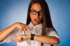 Stressed woman staring into watch gesturing being late Stock Photography