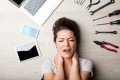 Stressed woman surrounded by hand tools stock image