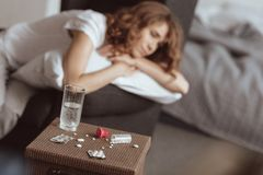 Stressed woman thinking about life and looking at pills. Selective focus on pills lying on a table while a depressed woman sitting in the background while having Royalty Free Stock Photo
