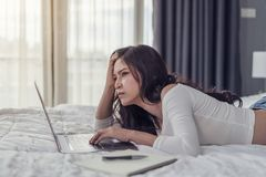 Stressed woman using laptop computer on bed Stock Image