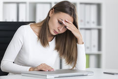 Stressed woman in white in office Royalty Free Stock Image