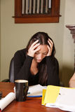 Stressed woman at work. Young woman puts head in hands, stressed and upset at work stock photo