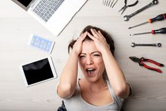 Stressed woman yelling with her hands to her hair stock photo