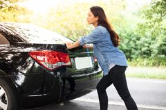 Stressed women after a car breakdown with Red triangle of a car stock photography