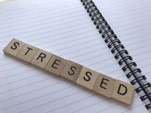 Stressed in wood alphabet letters on a notebook stock photos