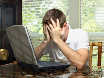 Stressed worker. Stressed male covering face while working the computer Royalty Free Stock Photo