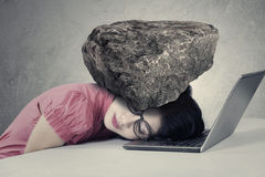 Stressed worker with a burden on her head. Picture of a stressed businesswoman sleeping over a notebook computer with a burden on her head royalty free stock photos