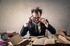 Stressed worker. Stressed man with books all over the place Stock Photography