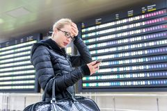 Stressed worried woman in international airport checking flight information on smart phone app. Stock Photography