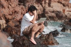 Stressed worried young Asian man with laptop sitting on the rock of sea shore suffering from severe depression.  Stock Images