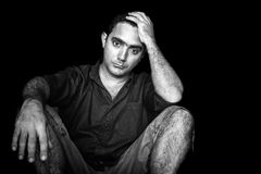 Stressed and worried young man sitting on the floor. Black and white image of a stressed and worried young man sitting on the floor  on a black background Stock Image