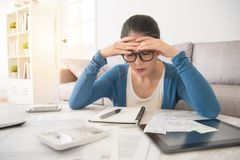 Stressed worried young woman doing banking. Beauty asian stressed worried young woman is doing banking and administrative work holding bills at home sitting on stock photos